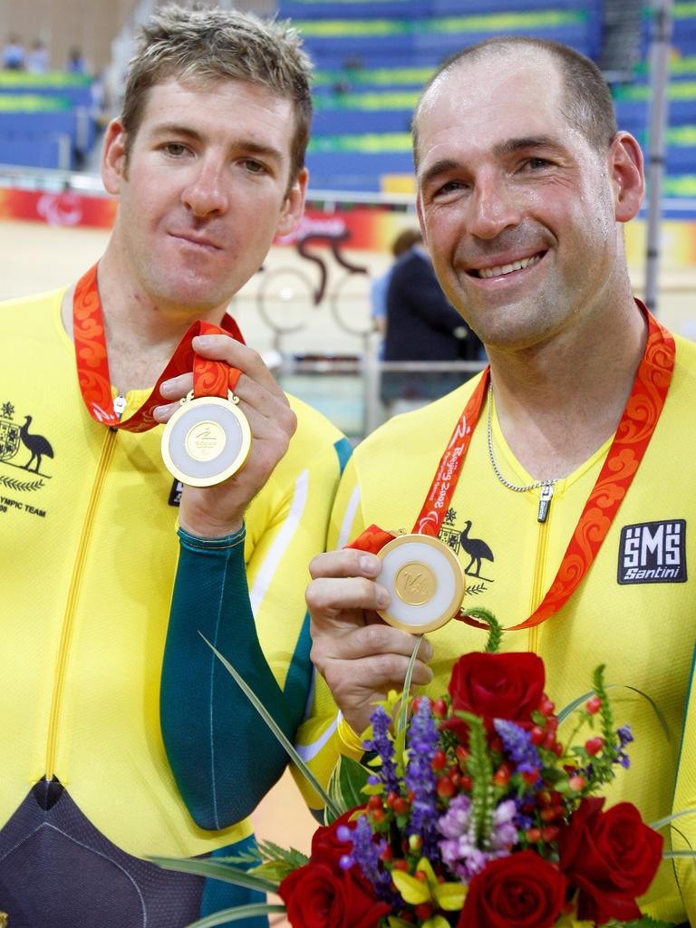 Kieran Modra, right, and his co-cyclist Tyson Lawrence, with their gold medals won for the 4000m individual pursuit at the Beijing Paralympic Games in 2008. Modra and Lawrence broke the world record at 4 minutes, 18.961 sec. Picture: AP / Andy Wong