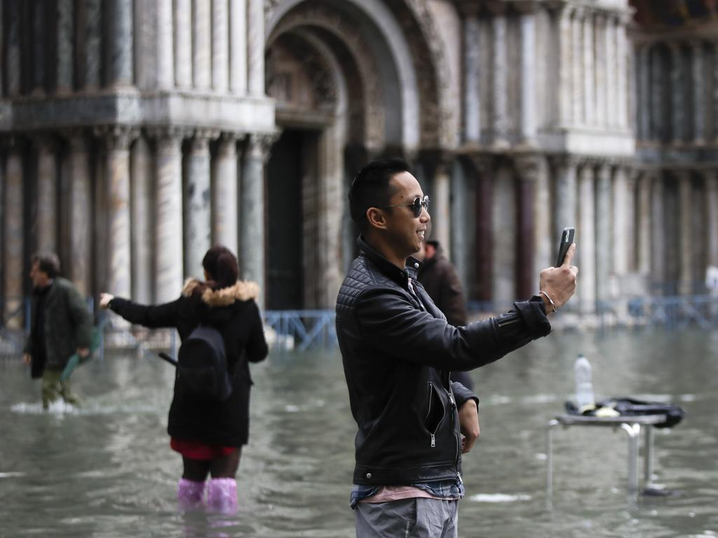 Tourists take pictures in a flooded St. Mark's Square, in Venice. Picture: AP