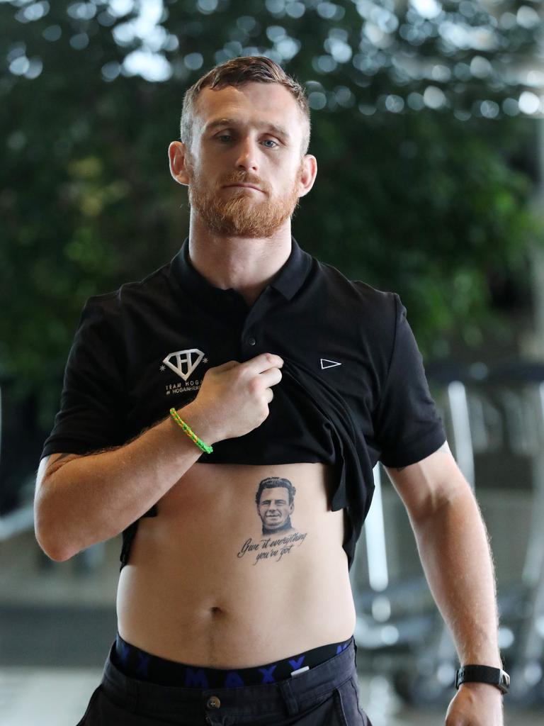 World boxing title challenger Dennis Hogan at Brisbane Airport yesterday with his new tattoo of his grandfather Paddy Burke, including the words