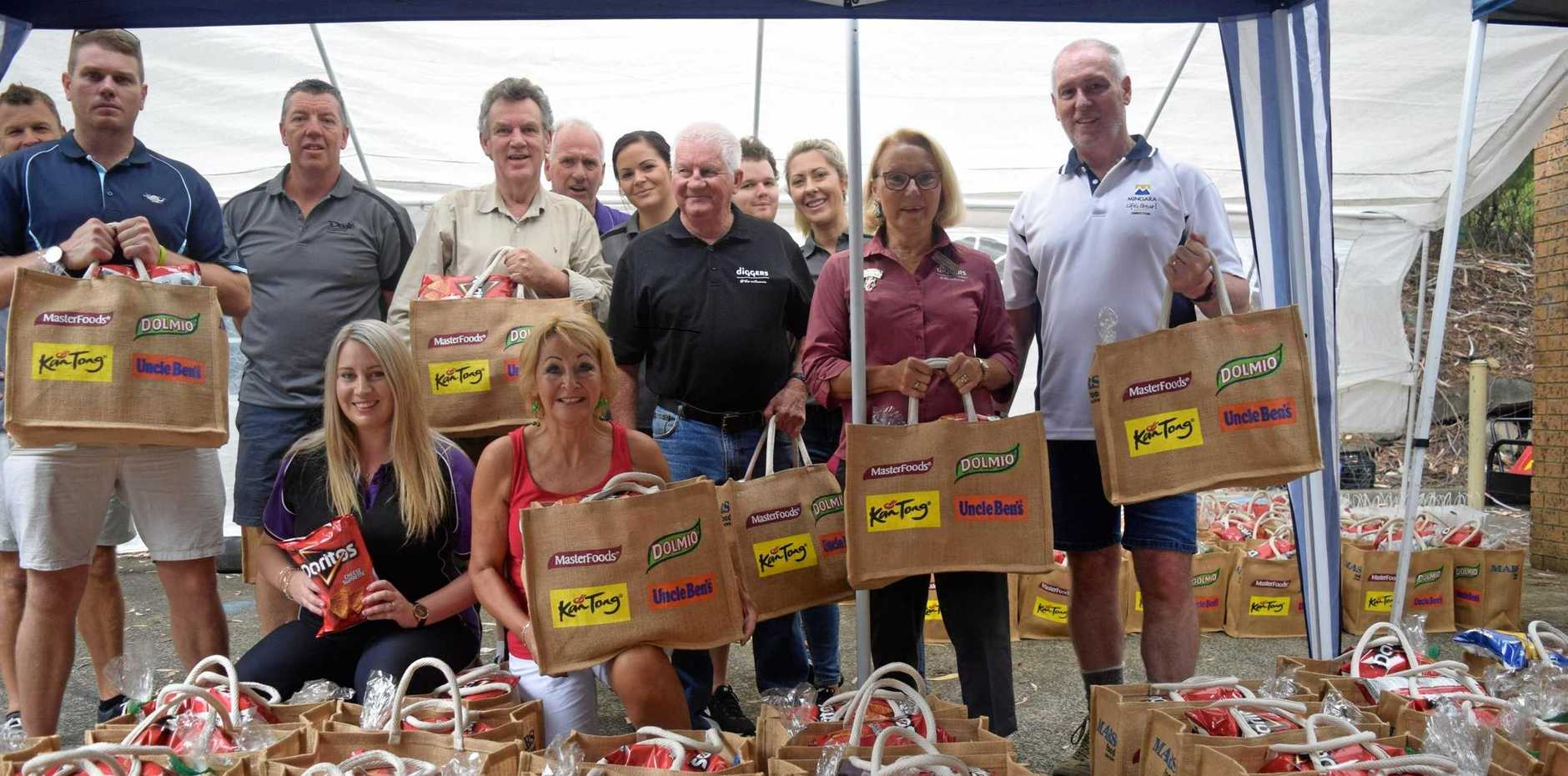 GIFT OF GIVING: Pastor Sandra Piefke (kneeling, centre) after last year's hamper packing with some of the heads of the different clubs and organisations who partner with House of Praise Christian Church, West Gosford, to make Operation Christmas Hamper an annual success.