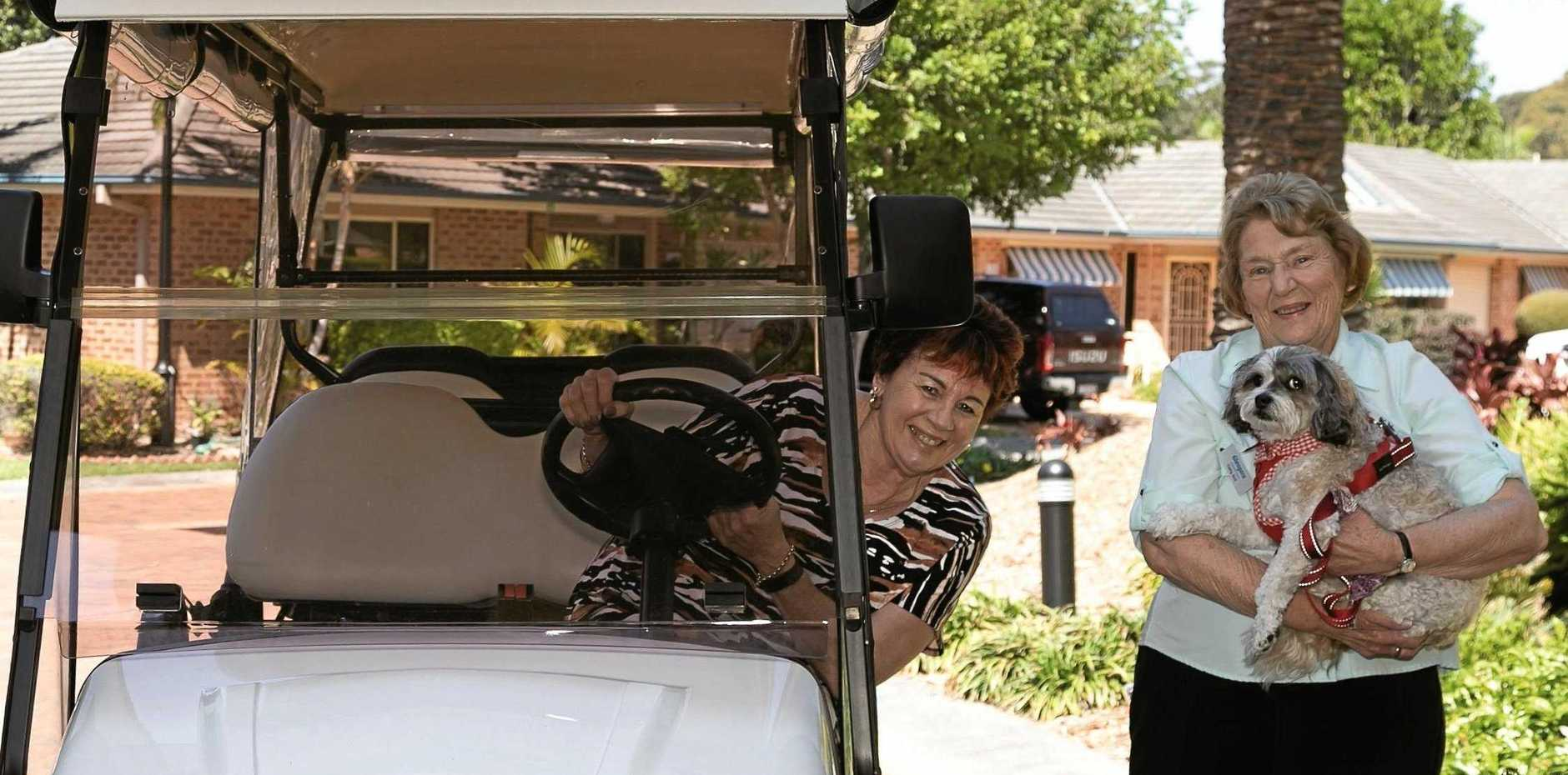 NEIGHBOUR-TO-NEIGHBOUR: Cathy Aird (right) with Rosie the dog and Brenda Carkeet at the wheel of the golf buggy transport, part of the service offered by 20 volunteers to make life better for fellow residents.