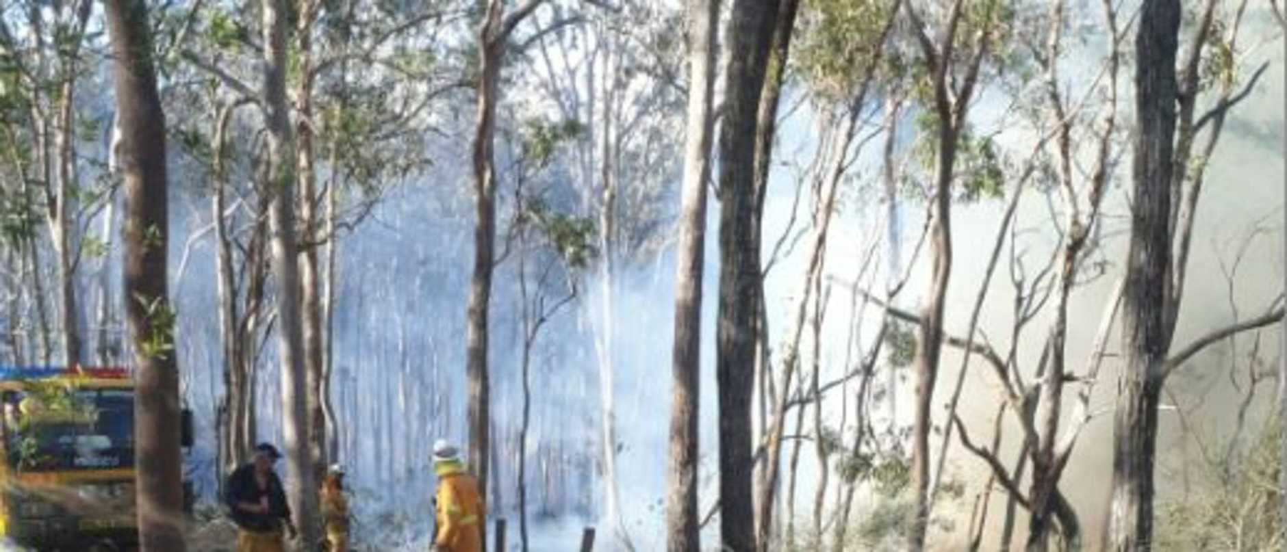 Firies on the front line near Widgee, earlier in the week. The fire is now contained on the eastern side, but winds and roaring temperatures could make the salutation worse for today.