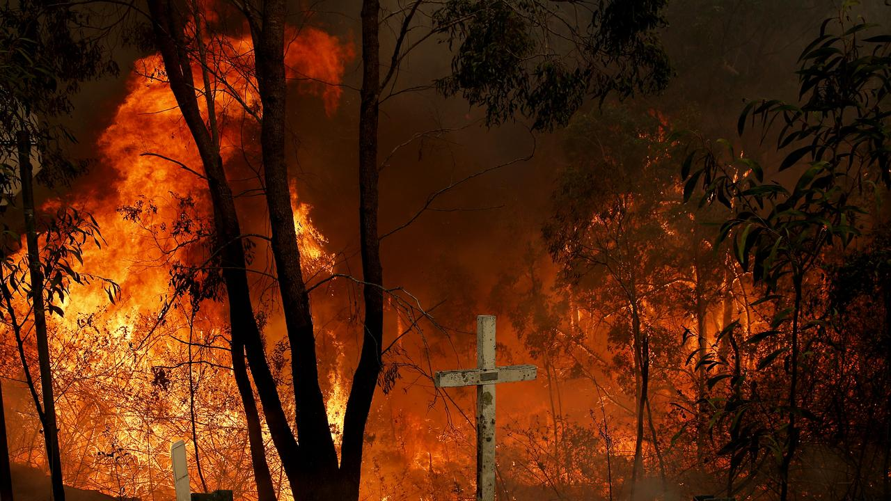 The Hillville bushfire burns out of control behind a memorial cross on the Pacific Highway at Possum Brush south of Taree in the Mid North Coast region of NSW, Tuesday, November 12, 2019. (AAP Image/Darren Pateman)