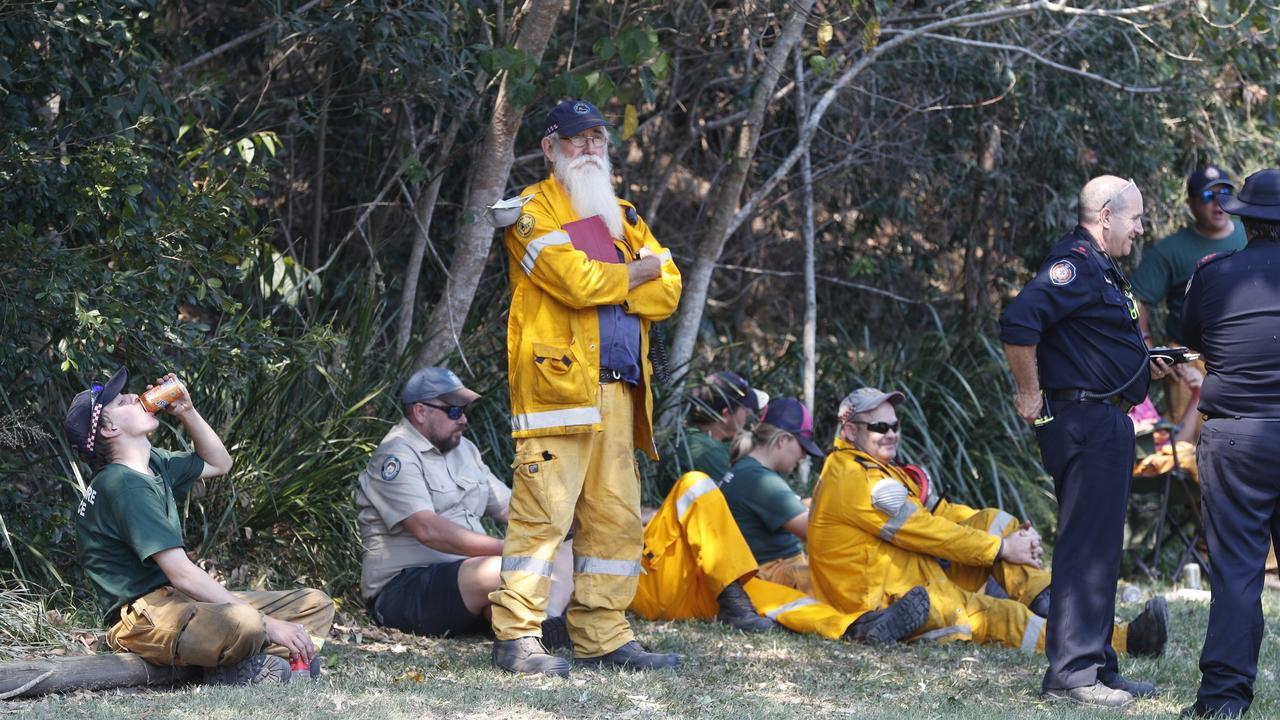 Firefighters and National Parks and Wildlife officers take a roadside break from the fire ground near Noosa Banks last Friday. They are a special group of people. Picture: Peter Wallis