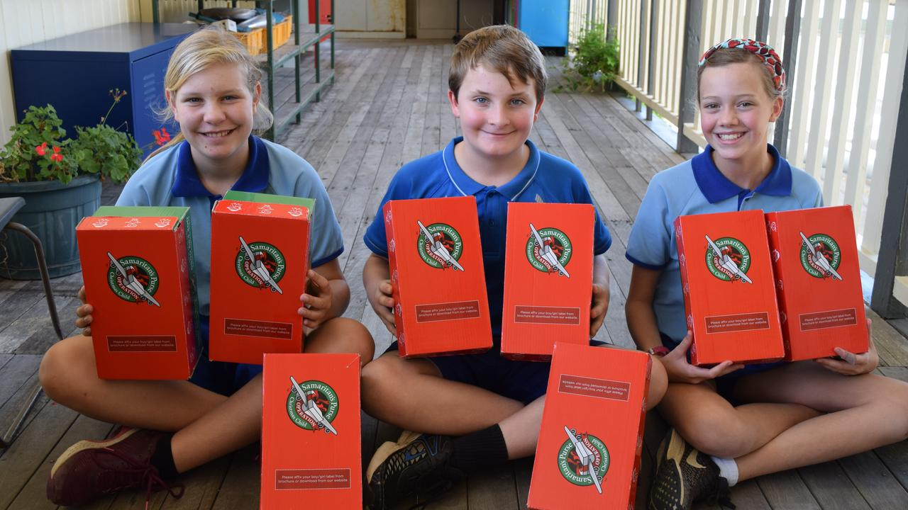 CHRISTMAS SHOE BOXES: Dallarnil State School Year 6 students Catherine White, Daniel Russell and Aneika Smith have been busy filling shoe boxes with goodies for a child in need overseas.