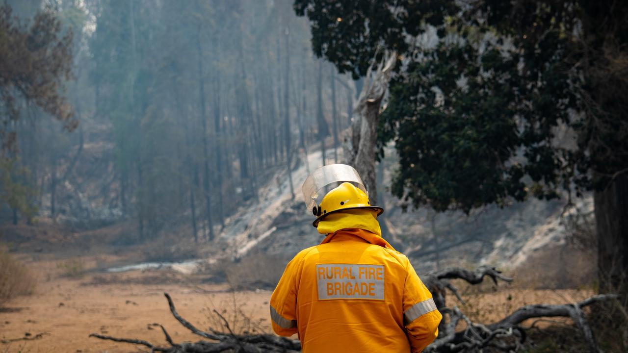 HELP: Mulgowie firefighter Roy Emerson inspects the damage at Thornton. Federal funding will help cover the costs of fighting the fires. PHOTO: ALI KUCHEL