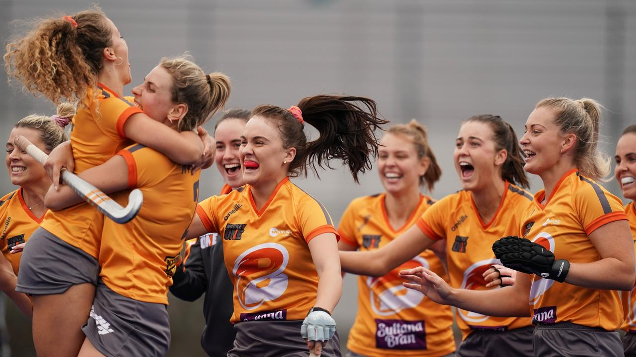 Ipswich hockey player Layla Eleison (with exposed mouthguard) joins her teammates celebrating their historic Hockey One national title success in Melbourne. Picture: Scott Barbour/ AAP