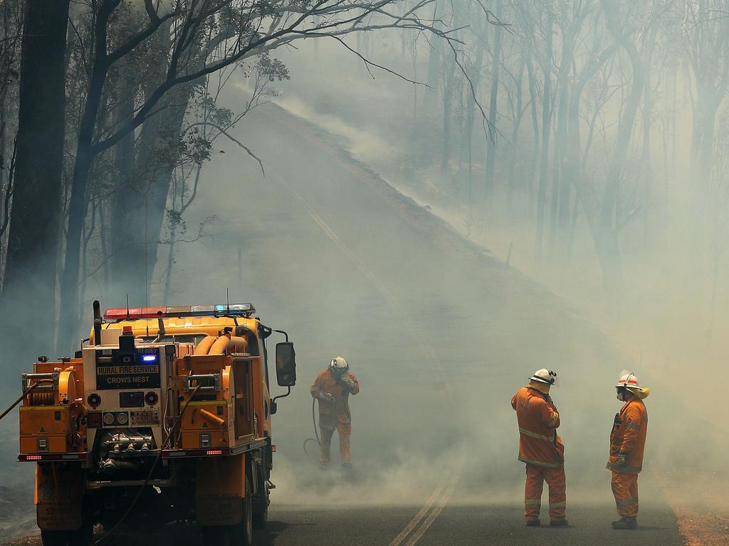 Rural Fire Brigade fighting a bush fire crossing Mount Jockey Rd, Ravensbourne. Photographer: Liam Kidston.