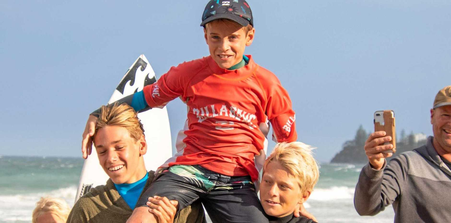 Evans Head surfer Max McGillivray is chaired up the beach after winning the under-12 boys division of the Billabong Parko's Grom Stomp.