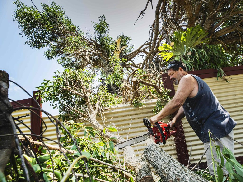 Palm Drive Resident Bill Carey cleans up the debris from a fallen tree on his fence and yard after a wild storm ripped through Mooloolaba on Sunday afternoon. Picture: Lachie Millard