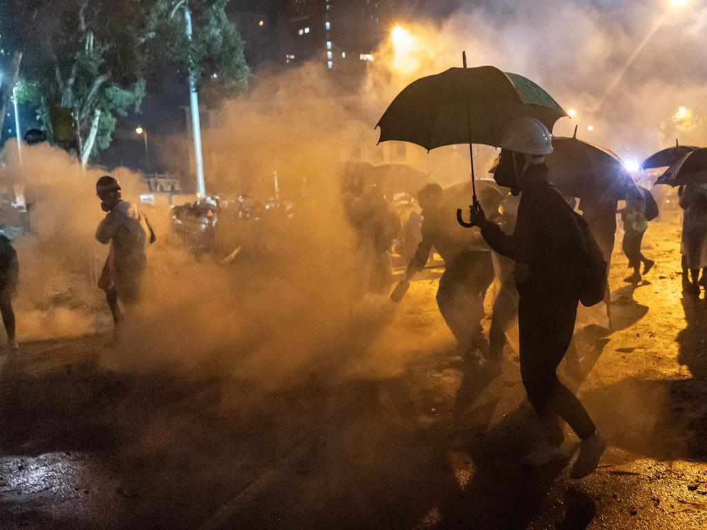 Protesters try to shield themselves from tear gas in Hong Kong today. Picture: Anthony Kwan/Getty Images