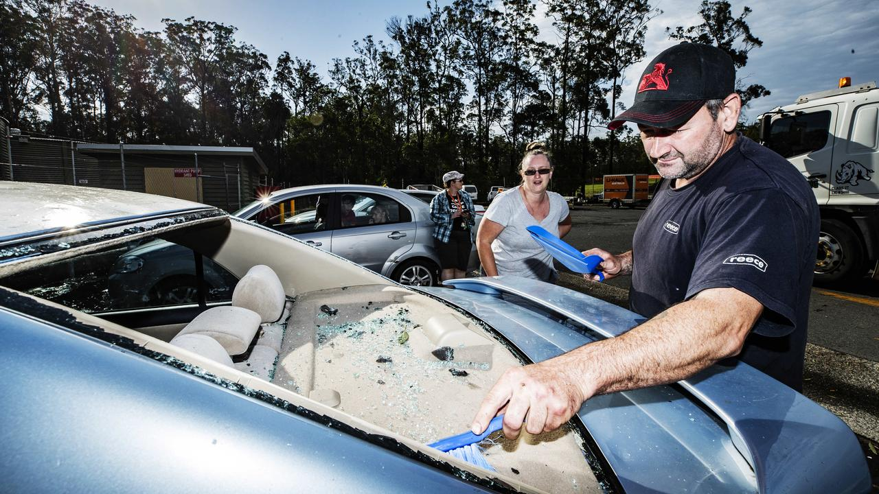 Sherry and Rick Duckworth from Gympie clean the glass out of their car after their back windscreen was shattered during a wild hailstorm at Glenview. Photo: Lachie Millard