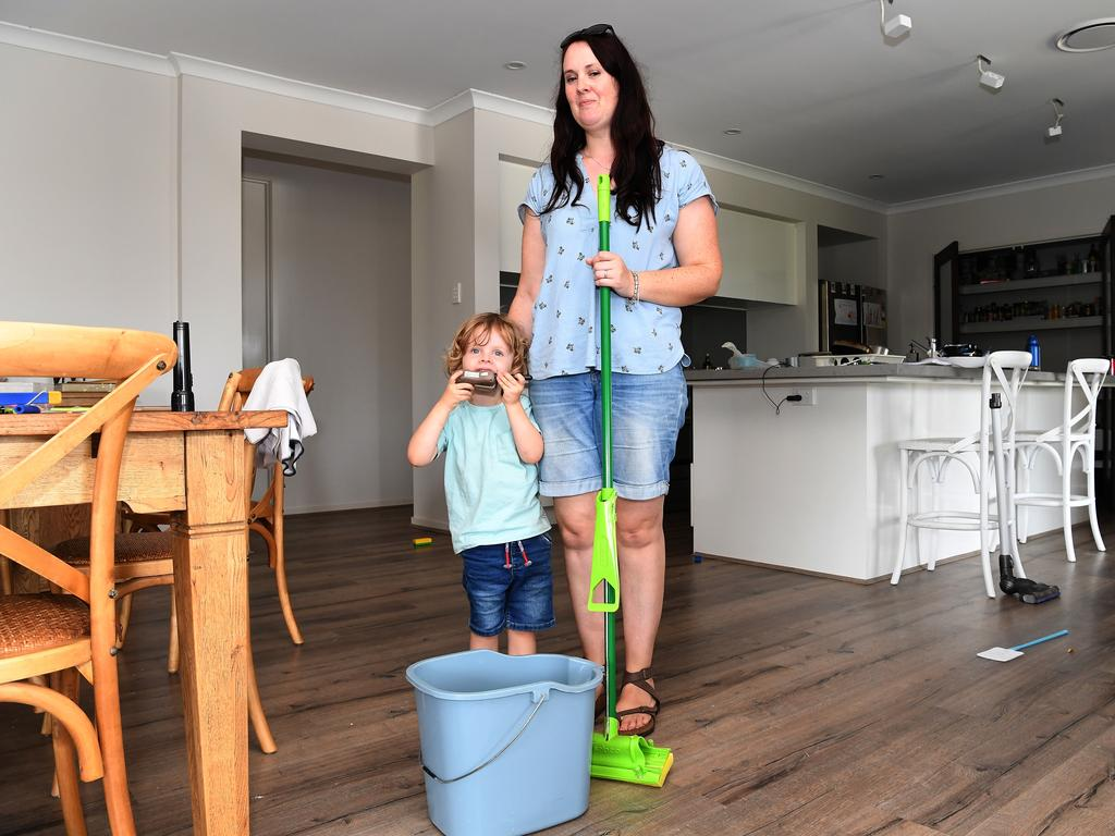 Cleaning up after the Sunday storm on the Sunshine Coast at Palmview. Catriona Wilson with son Alex mopping up after their roof suffered serious damage. Photo: Warren Lynam