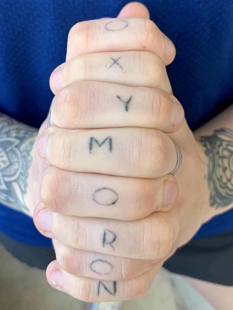 "Harris's new tattoo, which spells ""oxymoron"" on her fingers."