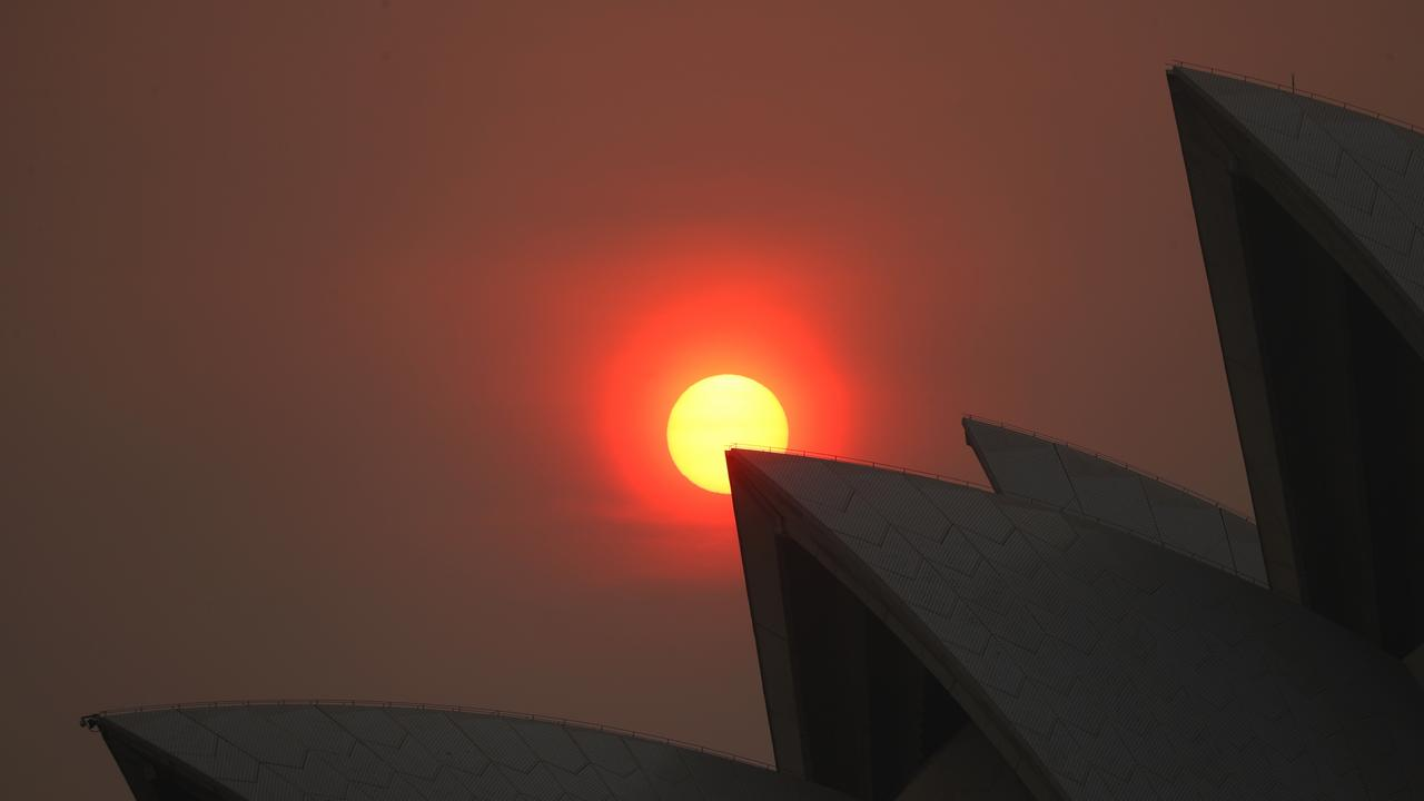 The thick smoke still hangs over Sydney which made for a spectacular red sun over the Opera House as it was rising. picture John Grainger