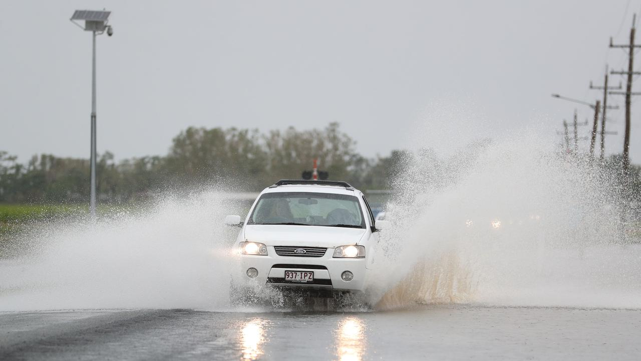 Cars drive along Shute Harbour Road near Proserpine through floodwaters. Picture: Peter Wallis