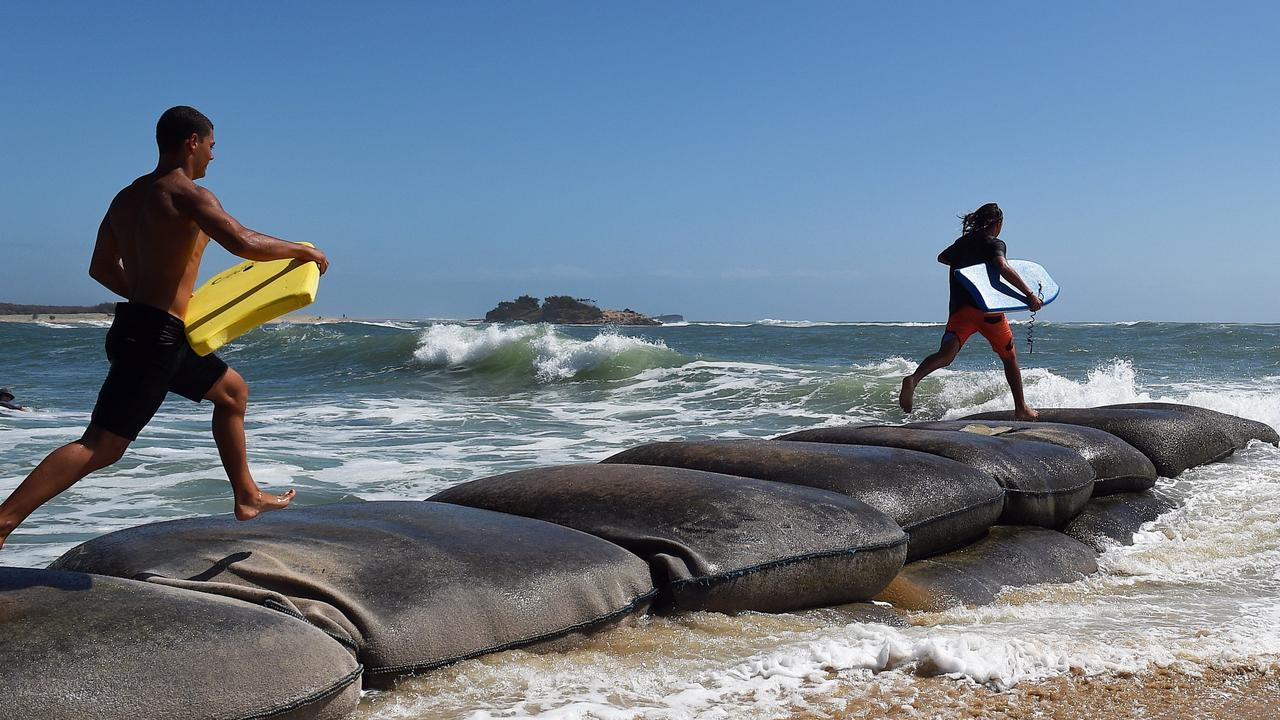 Gordan Marshman (yellow board) and Joel Grimley hit the surf on high tide at the Maroochy River mouth.