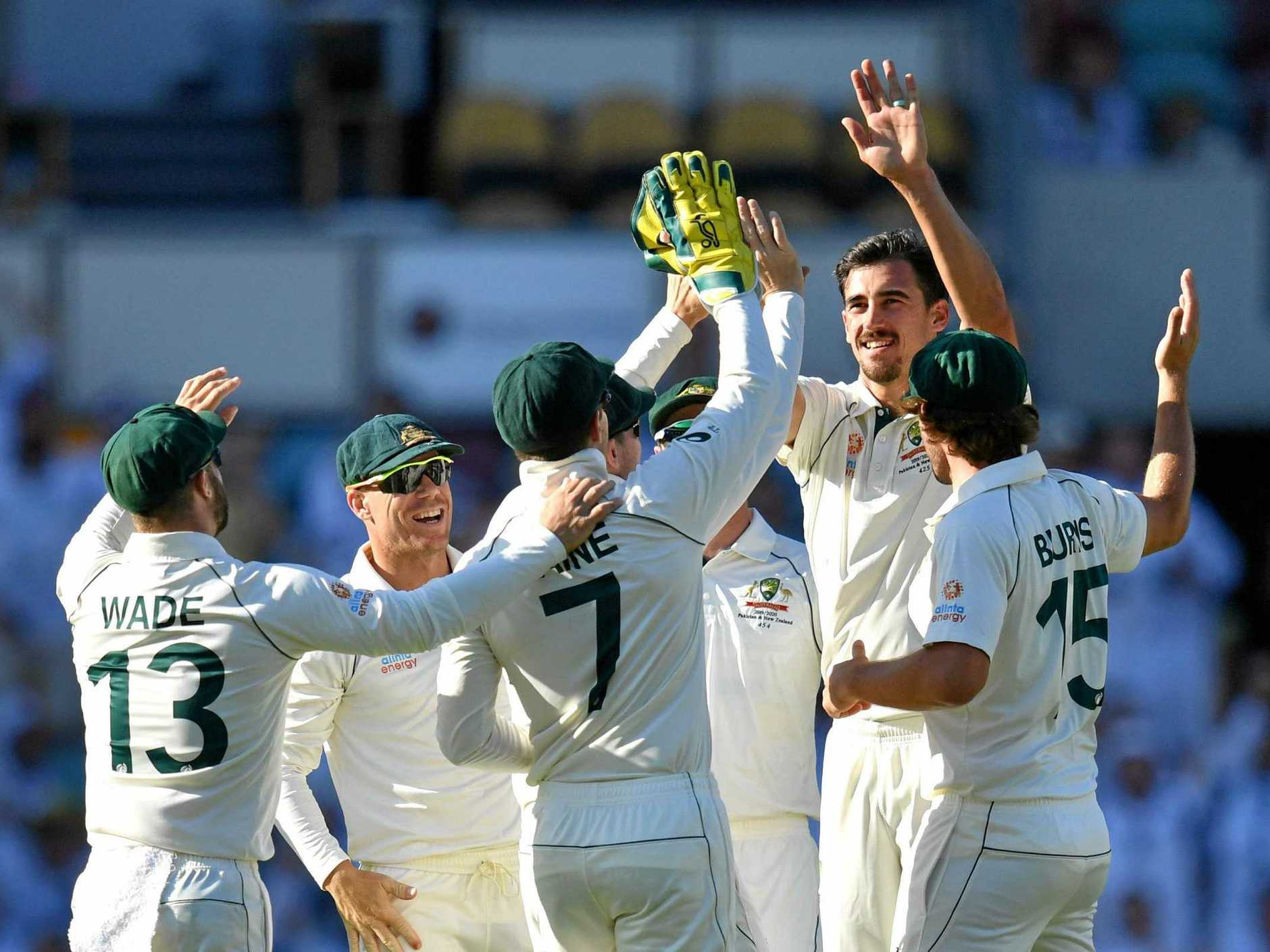 Mitchell Starc celebrates with teammates after getting the wicket of Haris Sohail at the Gabba on Saturday. Picture: Darren England/AAP