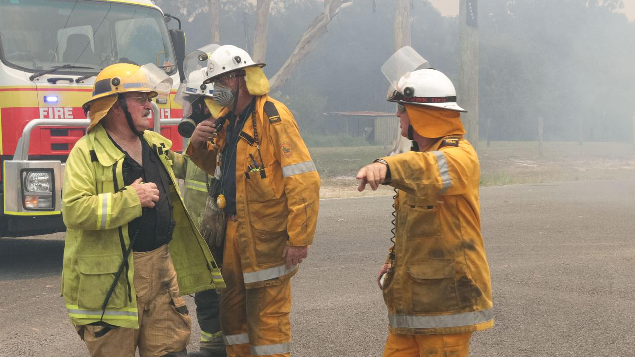 Firefighters discuss tactics on the front line of climate change during the Cooroibah bush fires which were to ultimately force the evacuation of Tewantin. (AAP Image/Rob Maccoll)