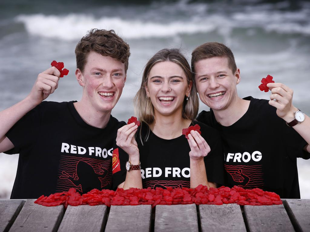 Red Frog volunteers Toby Scholes, Allegra Williams and Michael Donaldson armed with red frogs for Schoolies. Picture: David Caird
