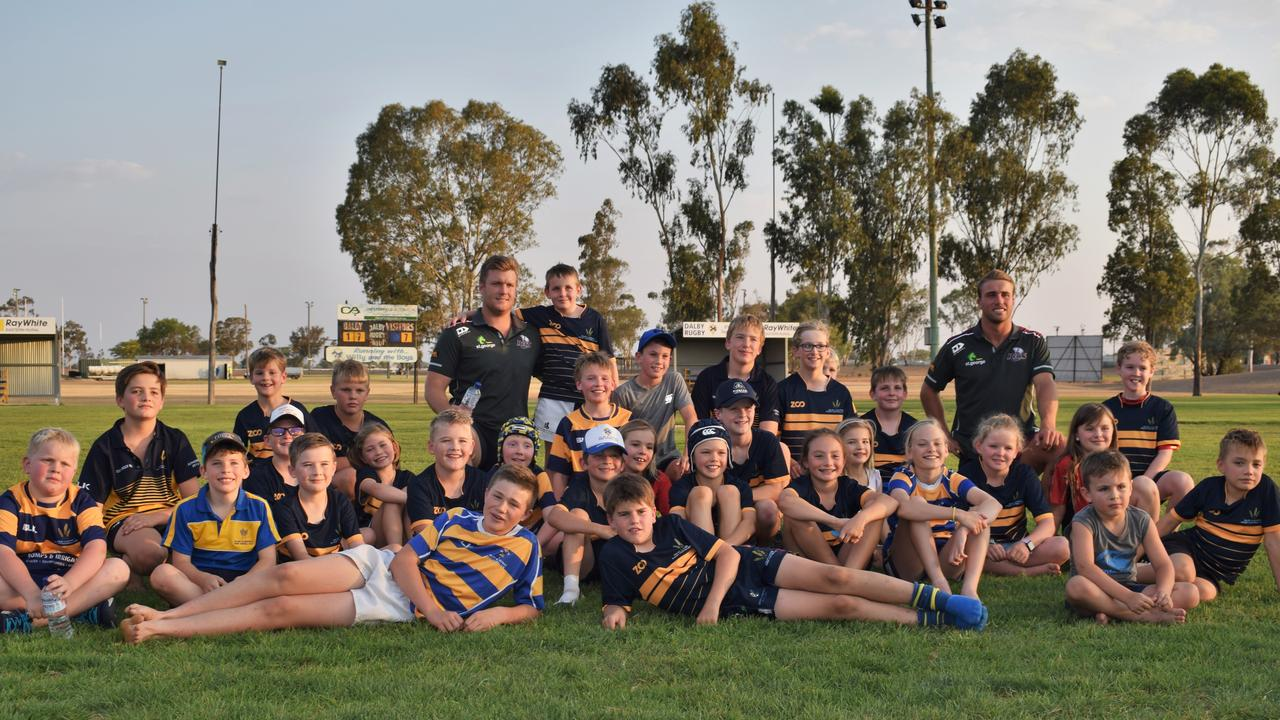 Dalby Wheatmen juniors meet Queensland Reds players Harry Hoopert (back left) and Hamish Stewart (back right) during the Reds-to-Regions tour. Photo: Emily Bradfield