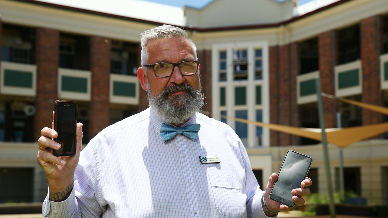 Cairns State High School principal Christopher Zilm with some of the banned devices, which will only be permitted to be used in one building. PICTURE: BRENDAN RADKE