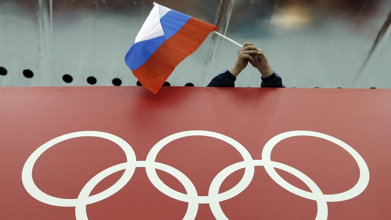 FILE - In this Feb. 18, 2014, file photo, a Russian skating fan holds the country's national flag over the Olympic rings before the men's 10,000-meter speedskating race at Adler Arena Skating Center during the Winter Olympics in Sochi, Russia. Formed with good intentions, the World Anti-Doping Agency finds itself at a crossroads as it celebrates its 20th anniversary at a conference this week in P