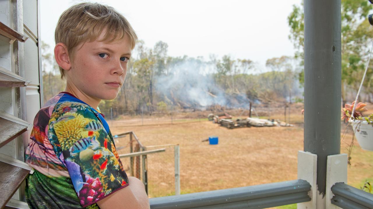 Charlie Hayward, 11, surveys the fire damage from the cubby house in his family's backyard near Sarina Beach.