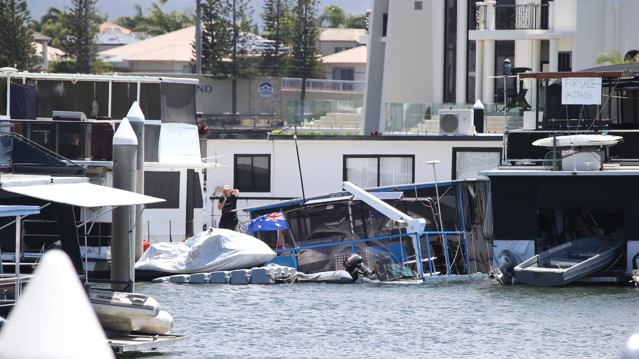 A man, believed to be the owner, ringing salvage crews in an effort to save his boat at Hope Island Marina. Picture Glenn Hampson