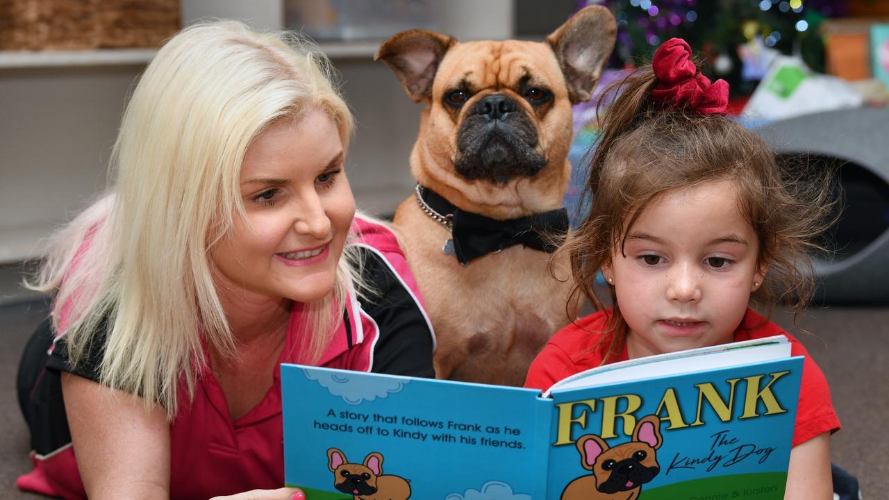 Frank the Kindy Dog looks impressed as C&K Walkerston kindergarten teacher/director Peta Baxter and Rayna Nikolic read the book written about him.
