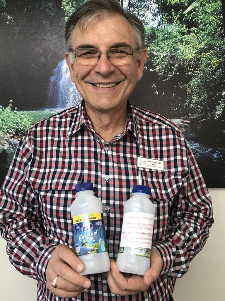 Tablelands Regional Mayor Joe Paronella with Malanda Milk bottles containing messages on what needs to be done to save milk production in Queensland.