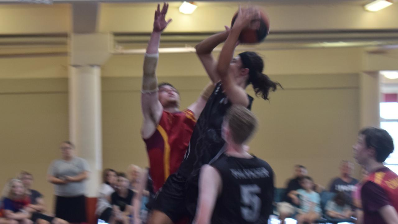 Gympie Basketball Association Grand Final Day – Pugs Linaker attempts a shot over the defence of Declan Bartolo.