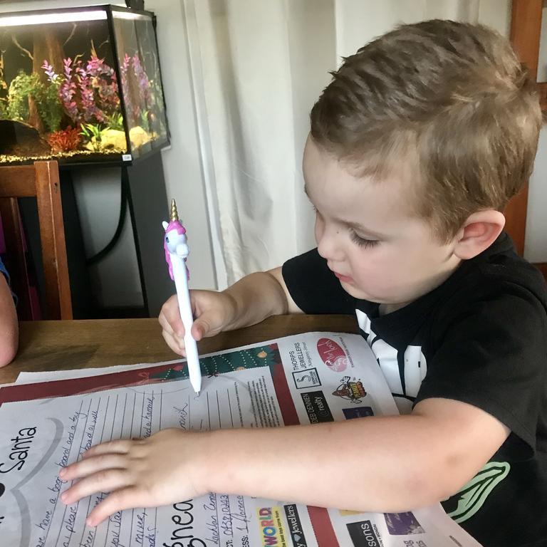 Lachlan Zenovich, 3, writes his Santa letter asking for a boogie board for Christmas.