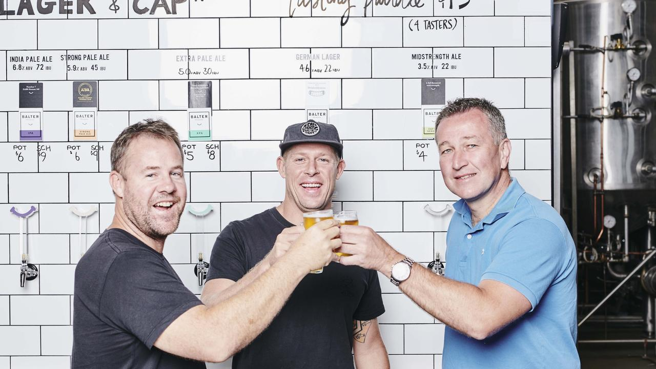 Ant Macdonald, Mick Fanning and CUB CEO Peter Filipovic celebrating the Balter Brewery deal.