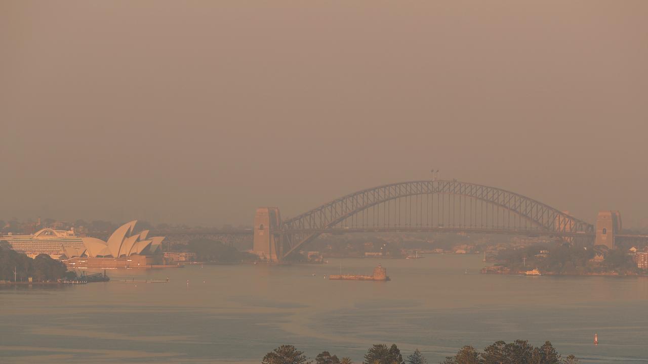 Smoke choking Sydney Harbour at dawn. Picture: John Grainger.