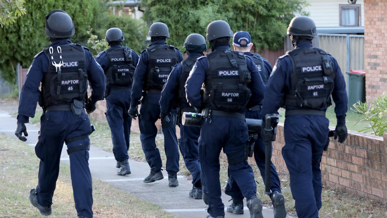 Tactical police walk towards a home they are about to raid in Mount Druitt.