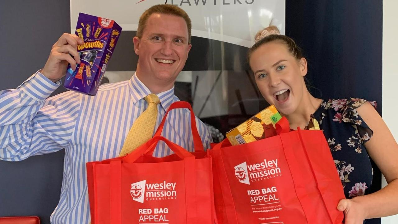 Creevey Russell Lawyers Practice Manager Tony McCallum and lawyer Isabella King do their bit to spread Christmas cheer as part of the firm's support for the Big Red Bag Appeal.