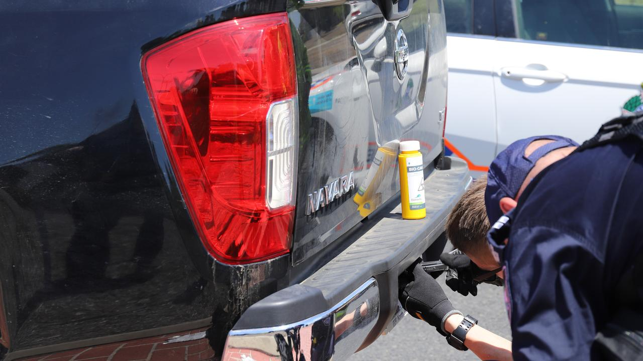 Police use a biohazard container as they searched the ute.