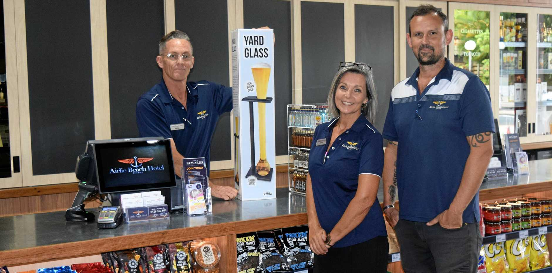 Airlie Beach Pub Liquor Store staff Kane Rogers and Christine Koolman with retail operations manager Chris De Marchi.