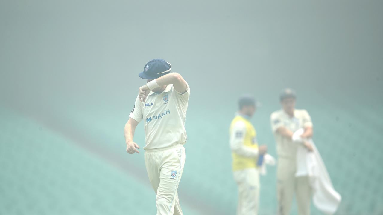 Players clear their eyes as smoke from the NSW bushfires envelops the ground. Picture. Phil Hillyard
