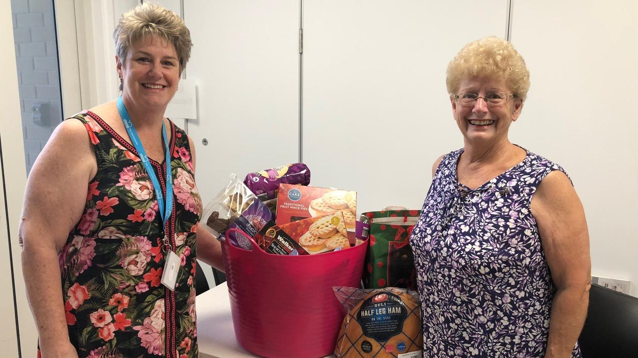 CHRISTMAS SPIRIT: Peer Practitioner Karen Sullivan and Secretary of Quota Club Aileen Weeden giving a Christmas Hamper to Step Up Step Down facility