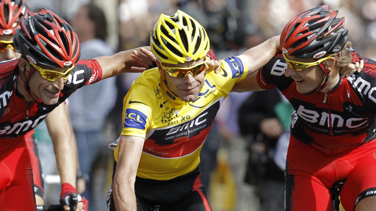 Cadel Evans is hugged by his BMC teammates as he crosses the finish line in the final stage of the 2011 Tour de France. Picture: AP