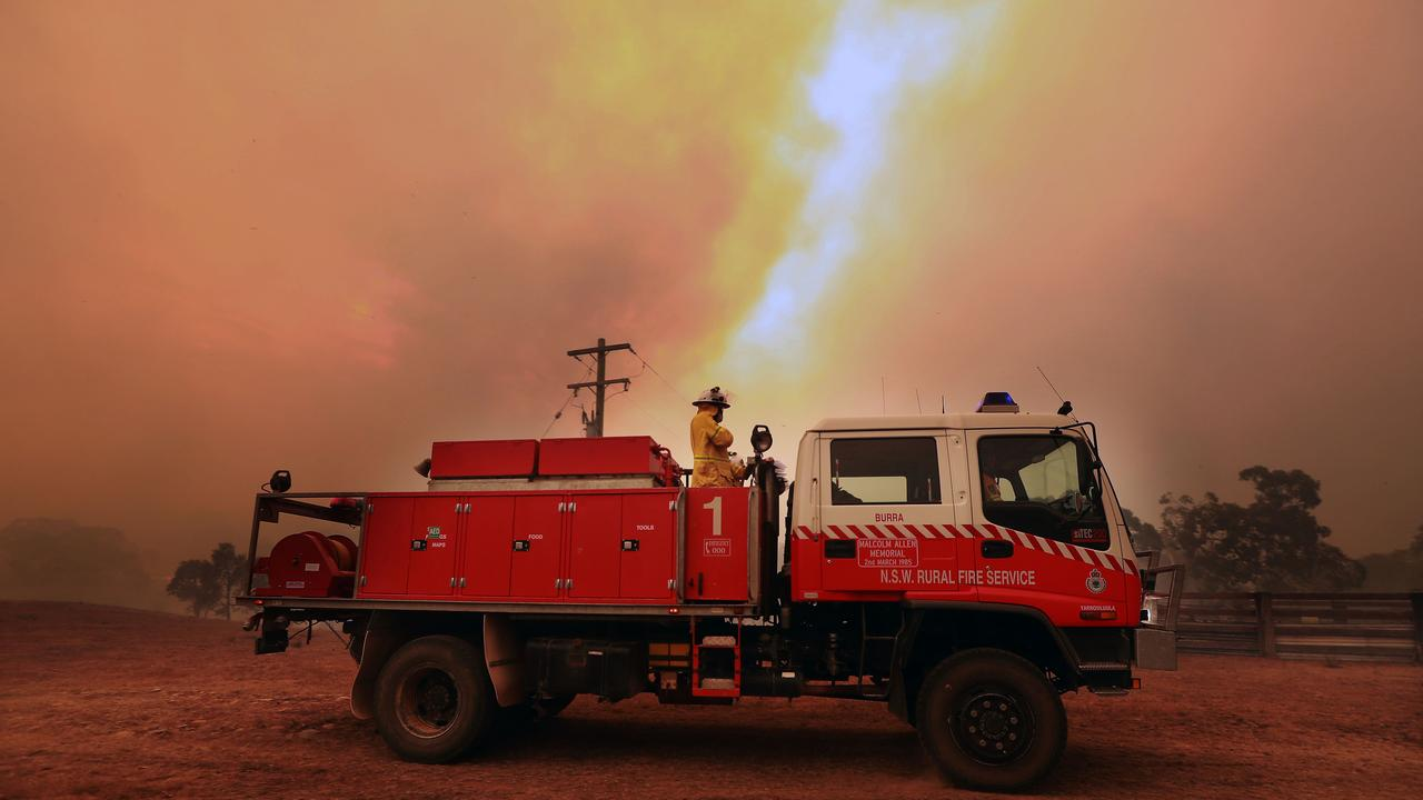 RFS volunteers from Carwoola prepare to protect property as a large fire burns out of control in the Bombay area just outside of Braidwood in NSW. Picture Gary Ramage