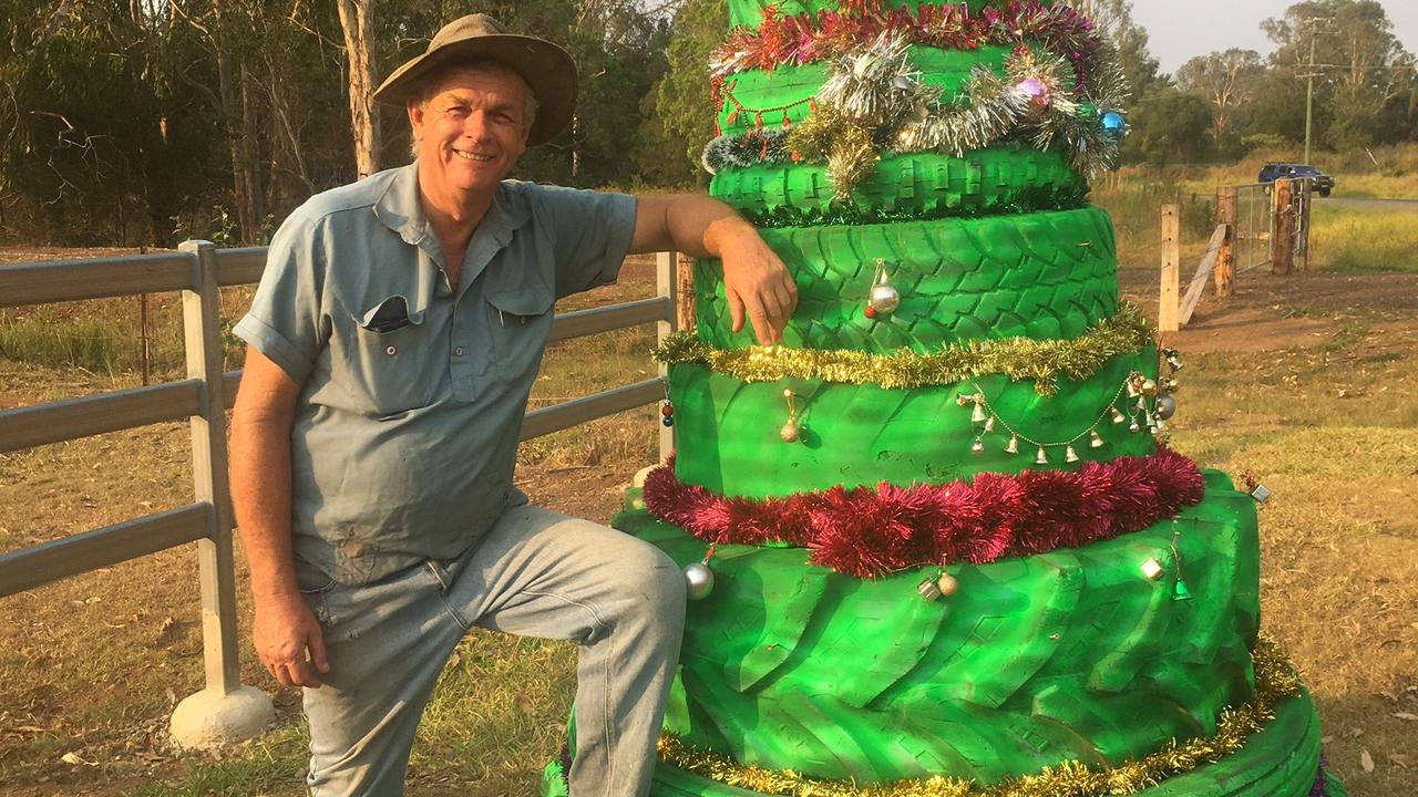 Gary Rozynski with his quirky Christmas tree made of unused tyres at his Imbil property this week. Photo: Linda Rozynski