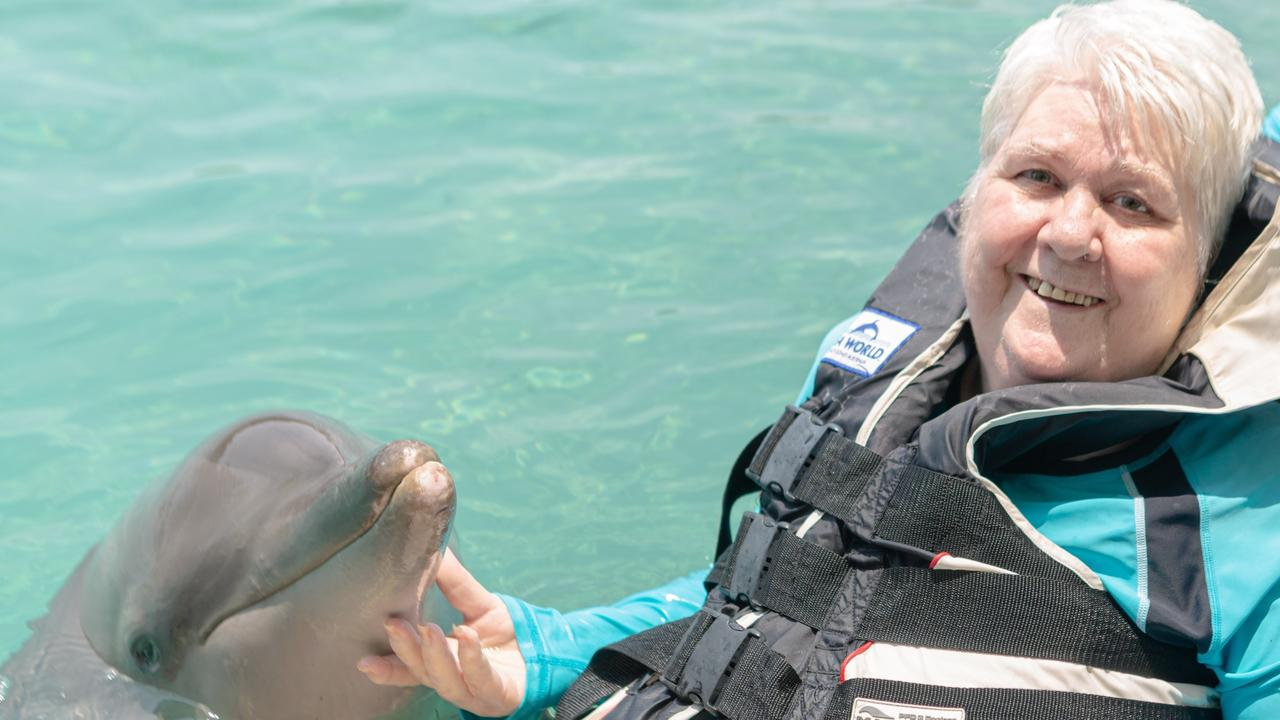 Shirley Mansell lives out a long-time dream in the Sea World pool with Howie the rescue dolphin.