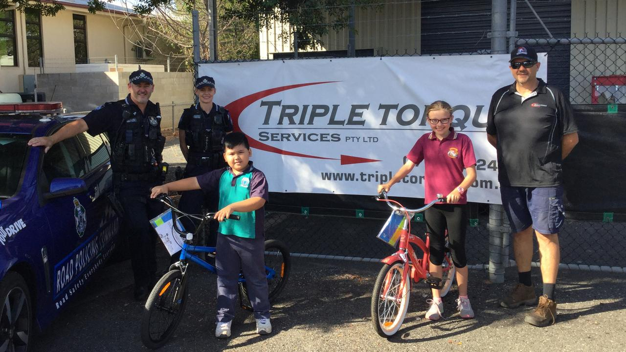 Constables Darren Rudling and Shannara Curran, the latest grand prize winners with their new bikes, Rafael Reyes from Emerald North State School and Ella McGuire from Denison State School and sponsor Brad Hughes.