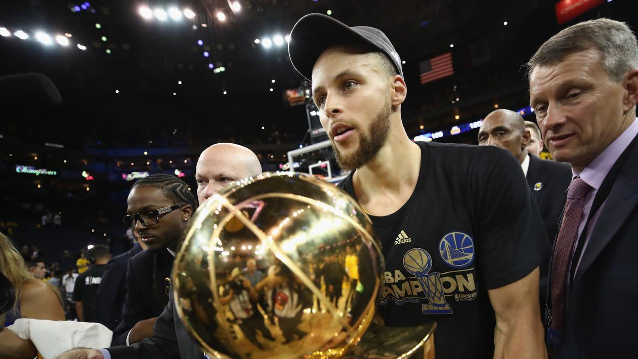 Stephen Curry cradles the Larry O'Brien trophy after his Warriors defeated Cleveland to take the 2017 NBA title. Picture: Getty Images