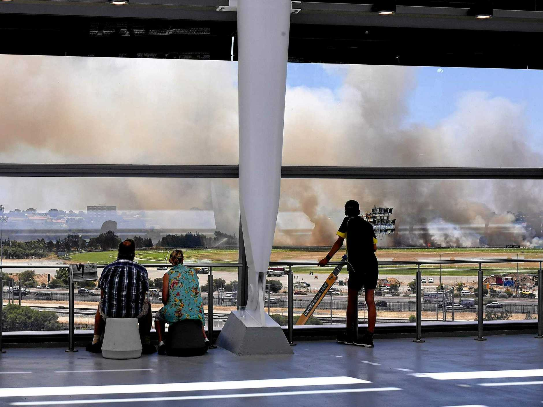 Spectators view a bushfire at Belmont Racecourse from Optus Stadium on day two of the first Test between Australia and New Zealand. Picture: Dave Hunt/AAP