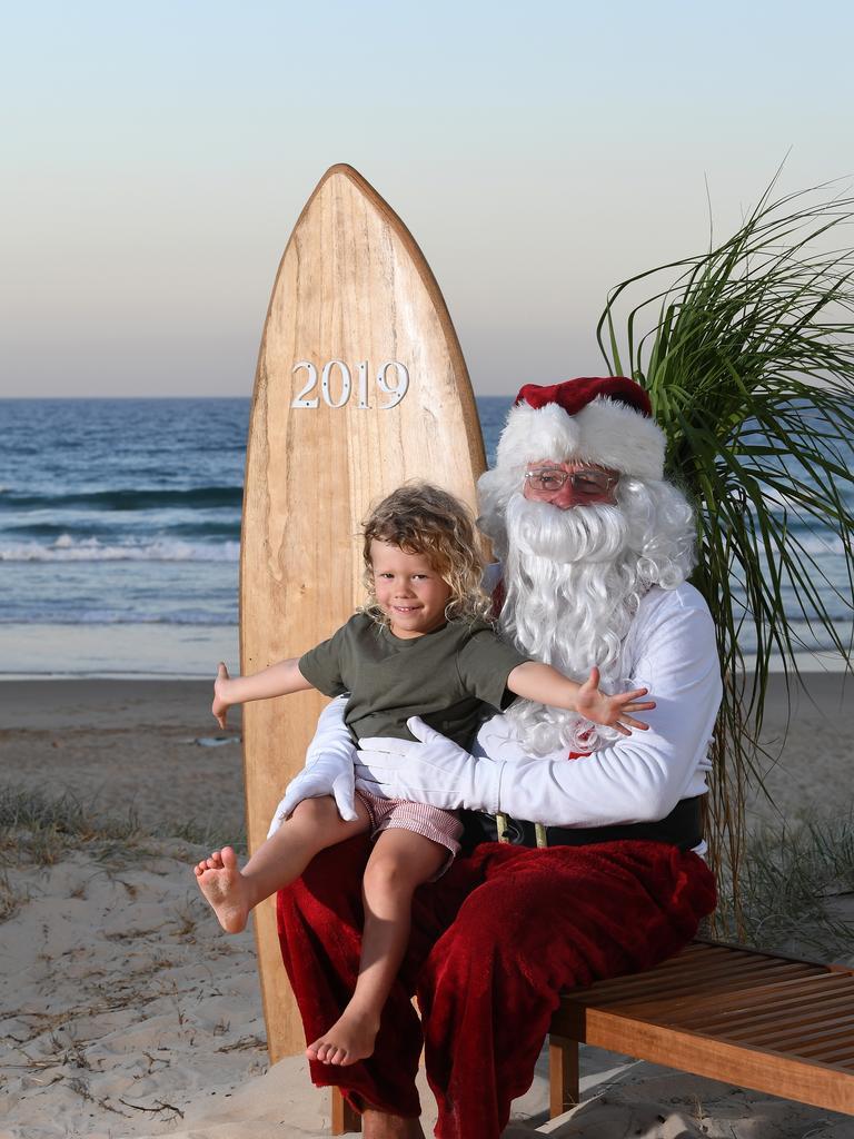 Ollie Sharpe, 4, with Santa at a 2019 Radley White Photography's Santa on the Beach photo shoot. Photo by Warren Lynam / Sunshine Coast Daily