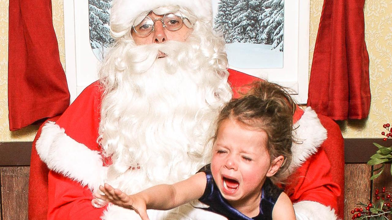 He may bring them presents, but some kids are less than impressed taking photos with Santa.
